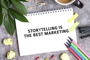 Storytelling is the best marketing on a notebook with a cup of coffee, compressed sheets, crayons, stapler