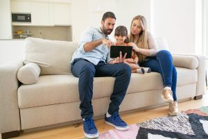 Happy family sitting on couch, using online app on tablet